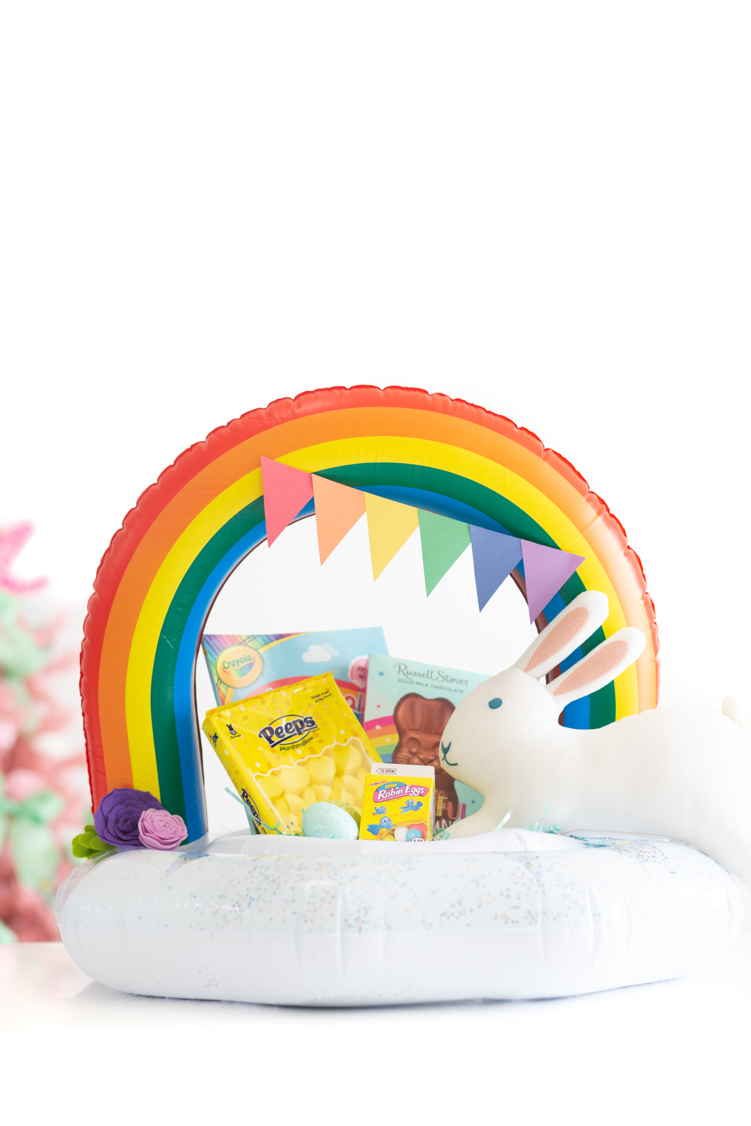 Rainbow pool float filled with Easter basket fillers like Peeps, Easter Candies, Coloring Books and Chocolate.