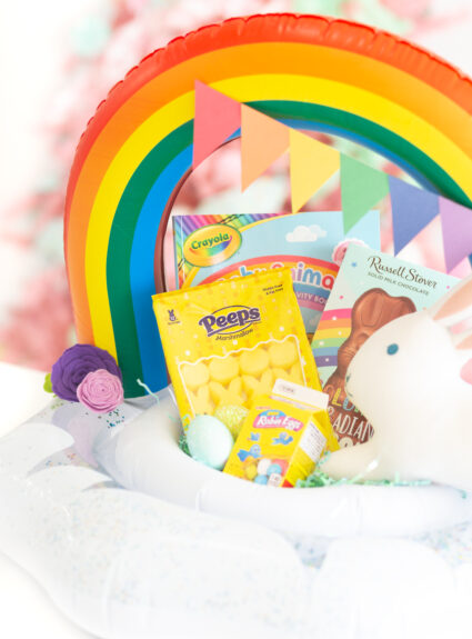 cute pool float easter basket that is rainbow themed, filled with matching items in rainbow colors such as yellow peeps, crayola coloring book, stuffed bunny