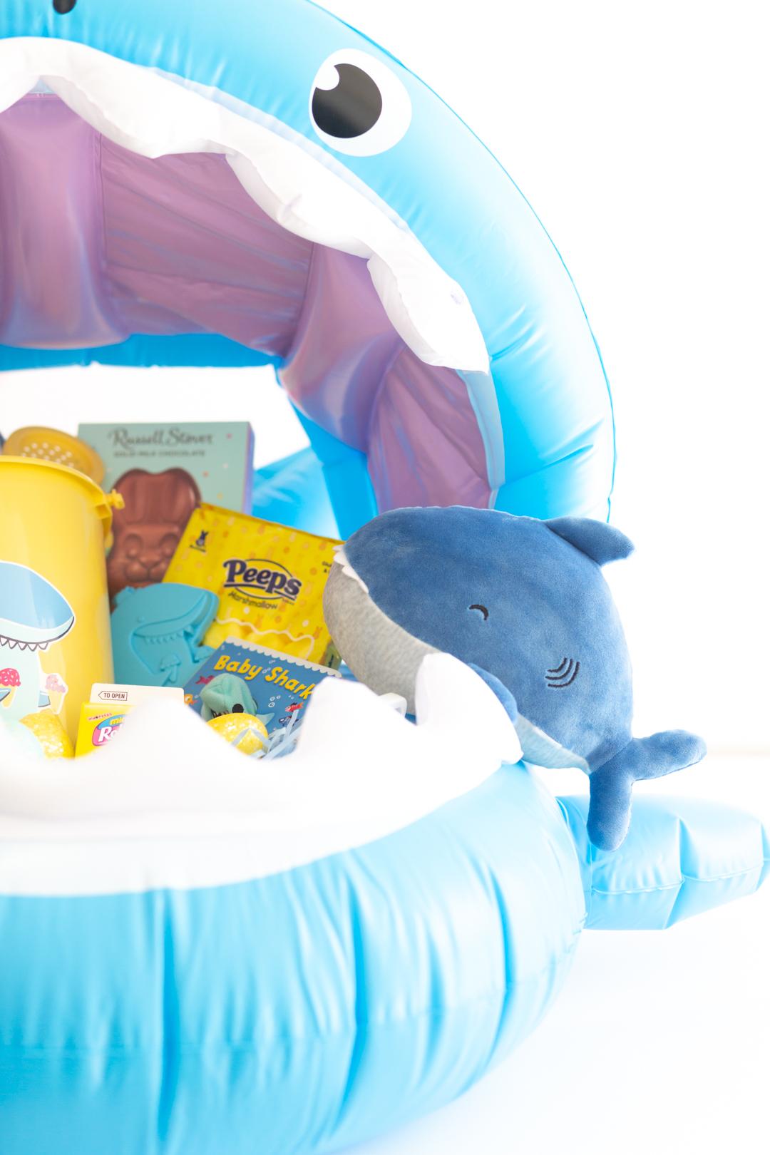 inside view of a shark themed gift basket with shark plush, shark pail set, shark book, peeps, easter bunny
