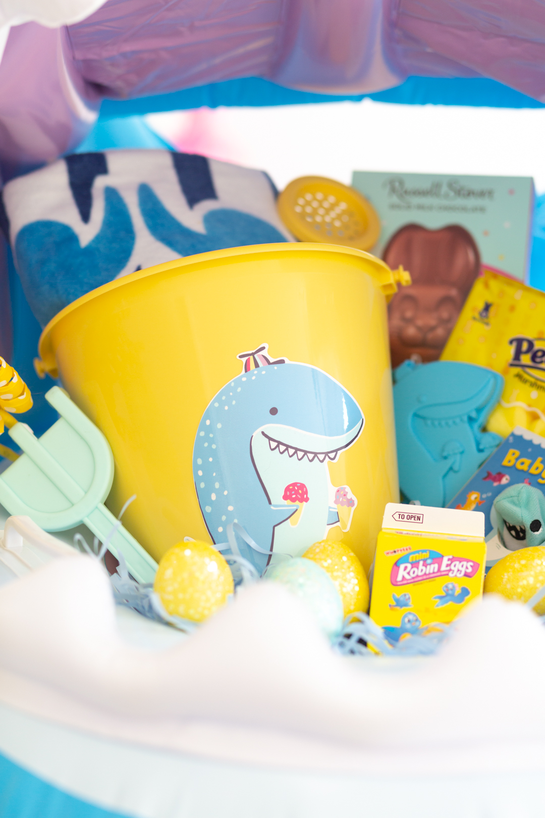 up close of shark easter basket with shark pail, beach towel, shovel, easter candy