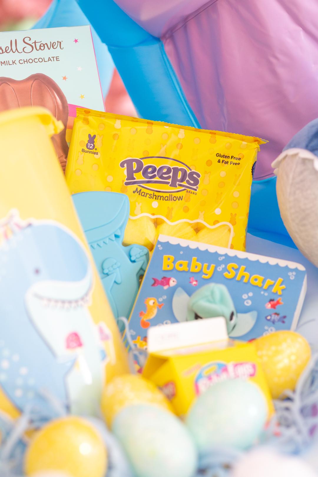 inside view of a big shark themed easter basket. Shark pail, yellow Peeps, baby shark book, plastic easter eggs.