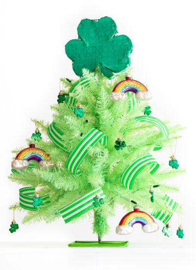 st. patrick's day tree using a mini lime green christmas tree with glass rainbow ornaments, green and white striped ribbon, mini shamrock ornaments and a mini shamrock piñata as a tree topper