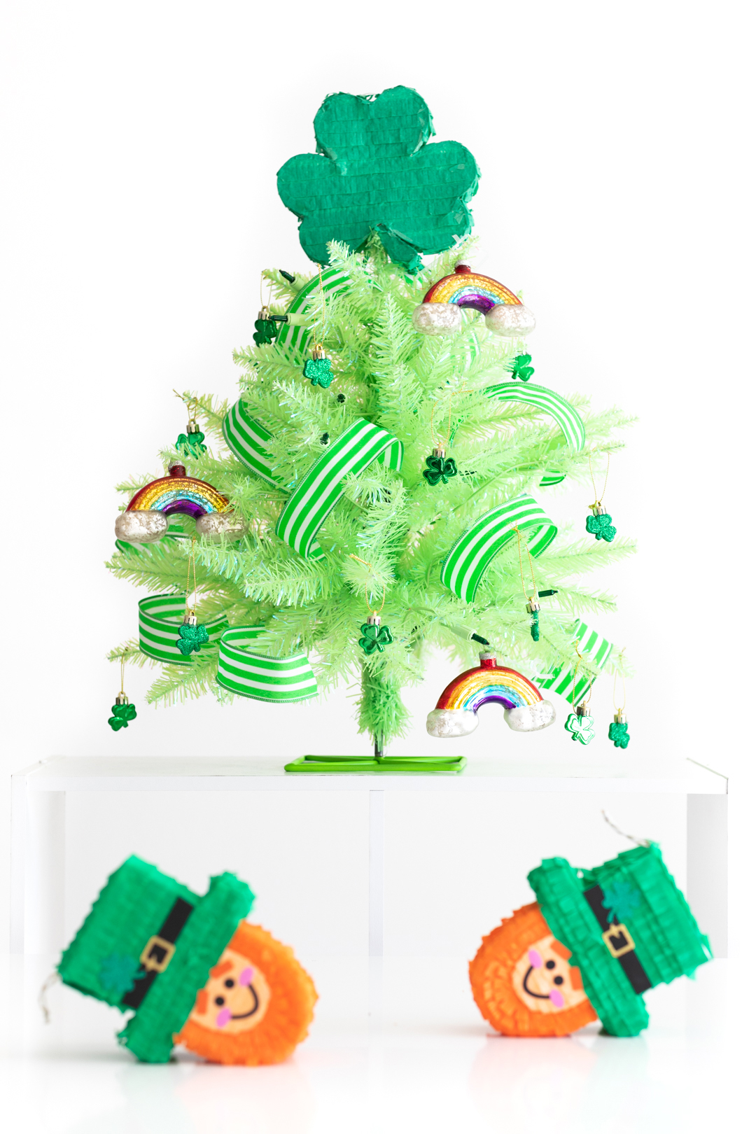 Mini green St. Patrick's Day tree, decorated with mini leprechaun piñatas nearby to decorate for St. Patrick's Day.