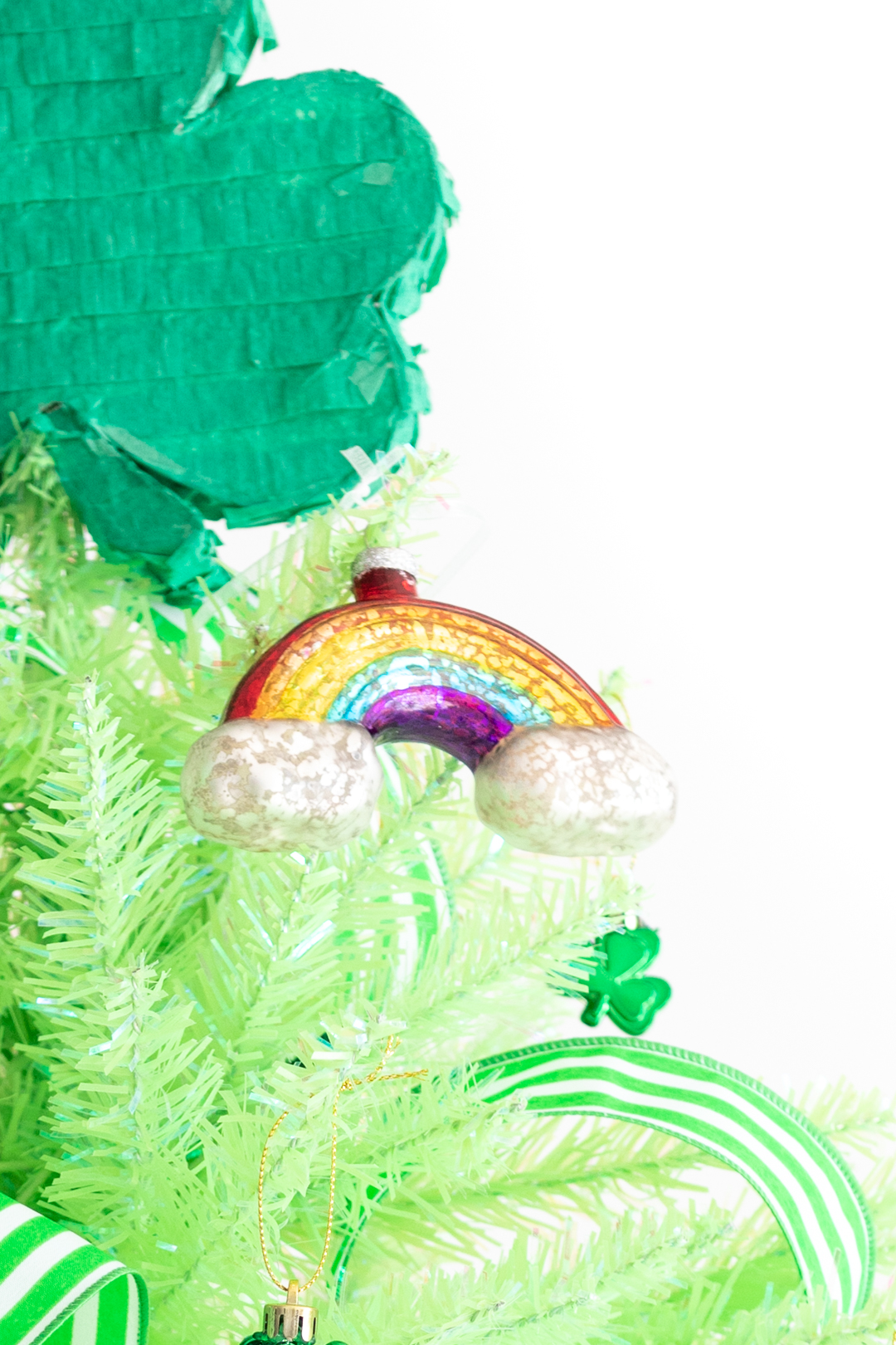 cute glass rainbow ornament hung on a lime green christmas tree used to celebrate St. Patrick's Day