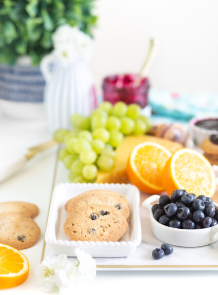 up close of a brunch board with crispy blueberry cookies and fresh fruits in the background