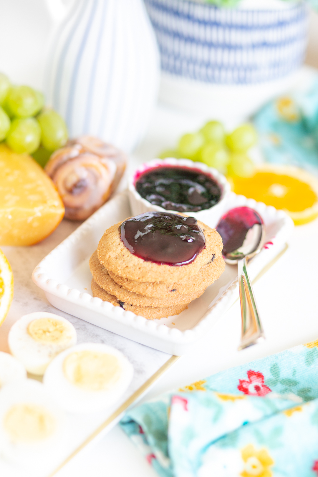stack of blueberry cookies on a brunch tray topped with blueberry jam and a spoon with jam on it