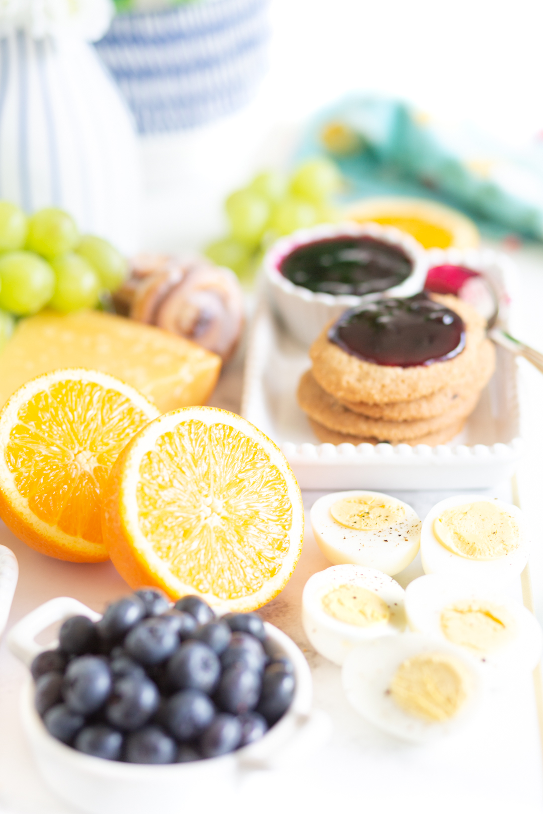 pretty brunch board with halved oranges, fresh blueberries, hard booked eggs
