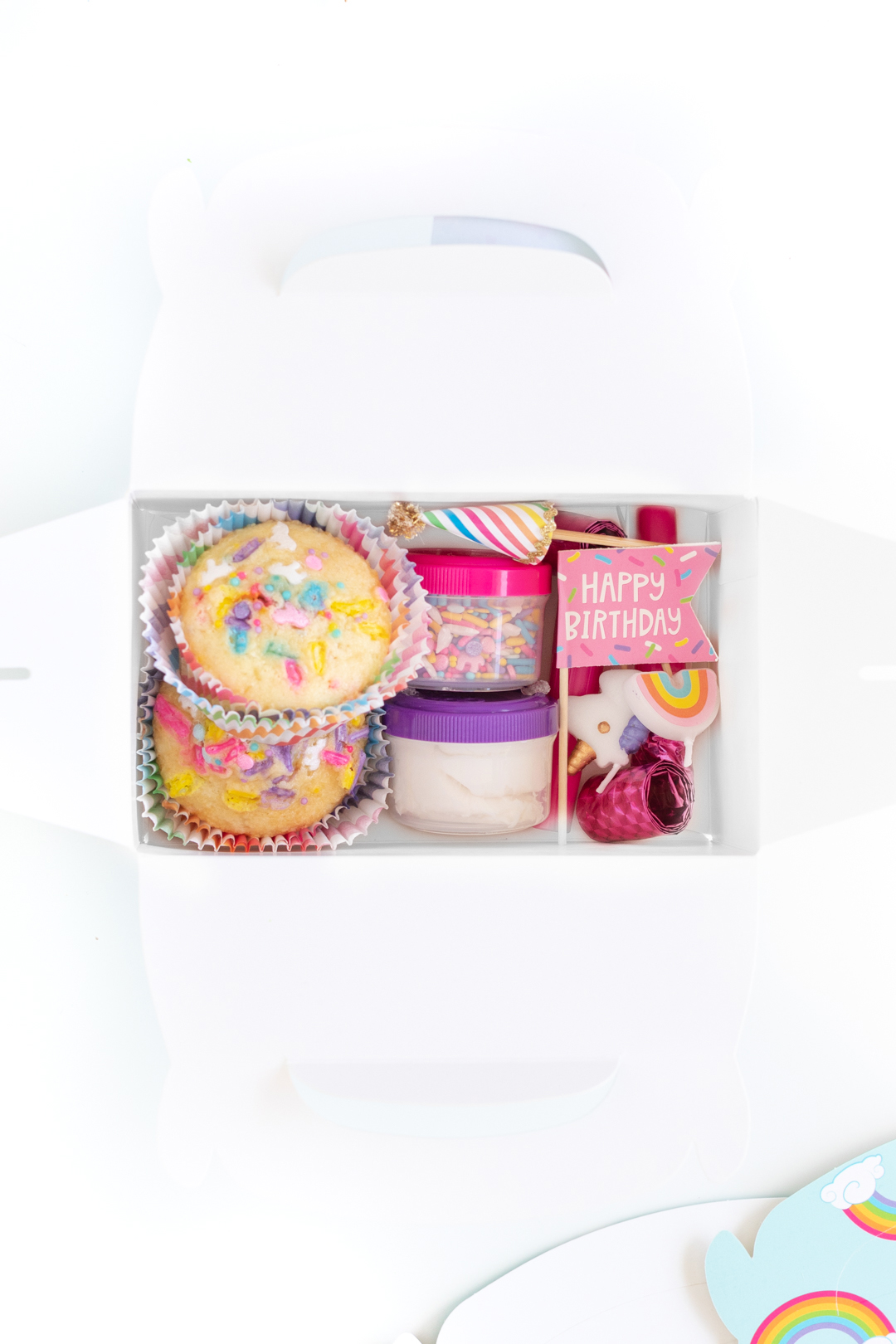 close up of items inside of a party favor box including funfetti style cupcakes, sprinkles and other birthday related trinkets