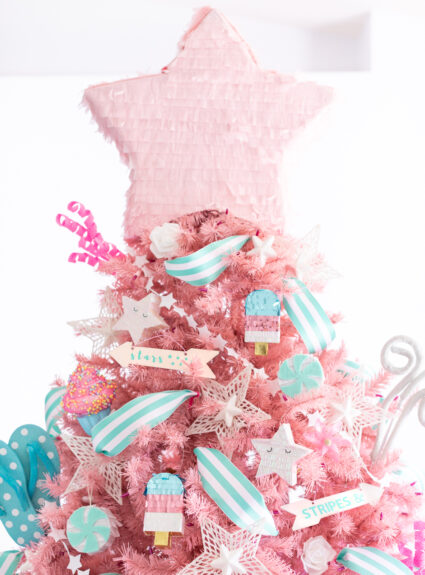 summer themed christmas tree with homage to patriotic holidays with stars, stripes and flip flops and popsicle pinatas as decorations