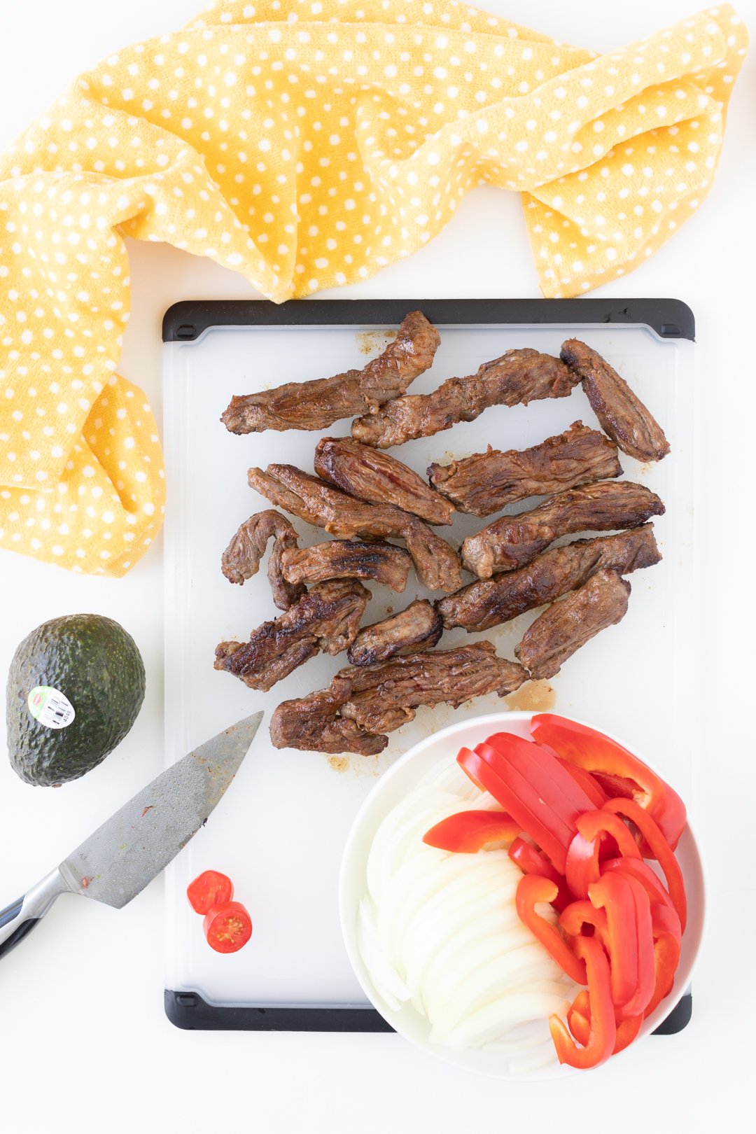 chopped steak strips on a cutting board with fresh cut peppers and onions nearby