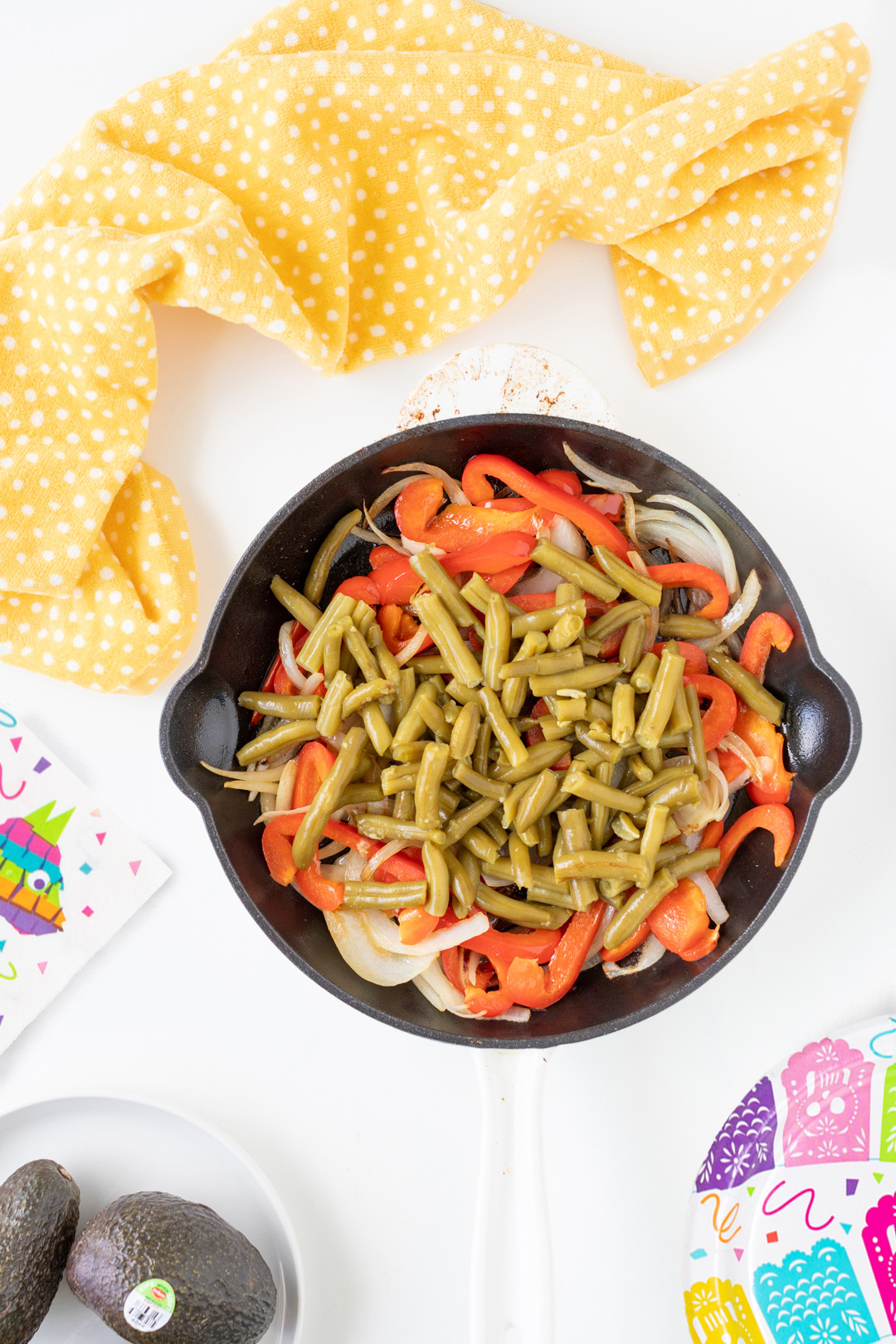 can of green beans added on top of cooked peppers and onions in a skillet