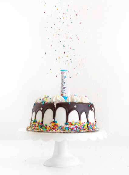 surprise candle loaded with edible confetti placed onto a simple birthday cake with a chocolate drip