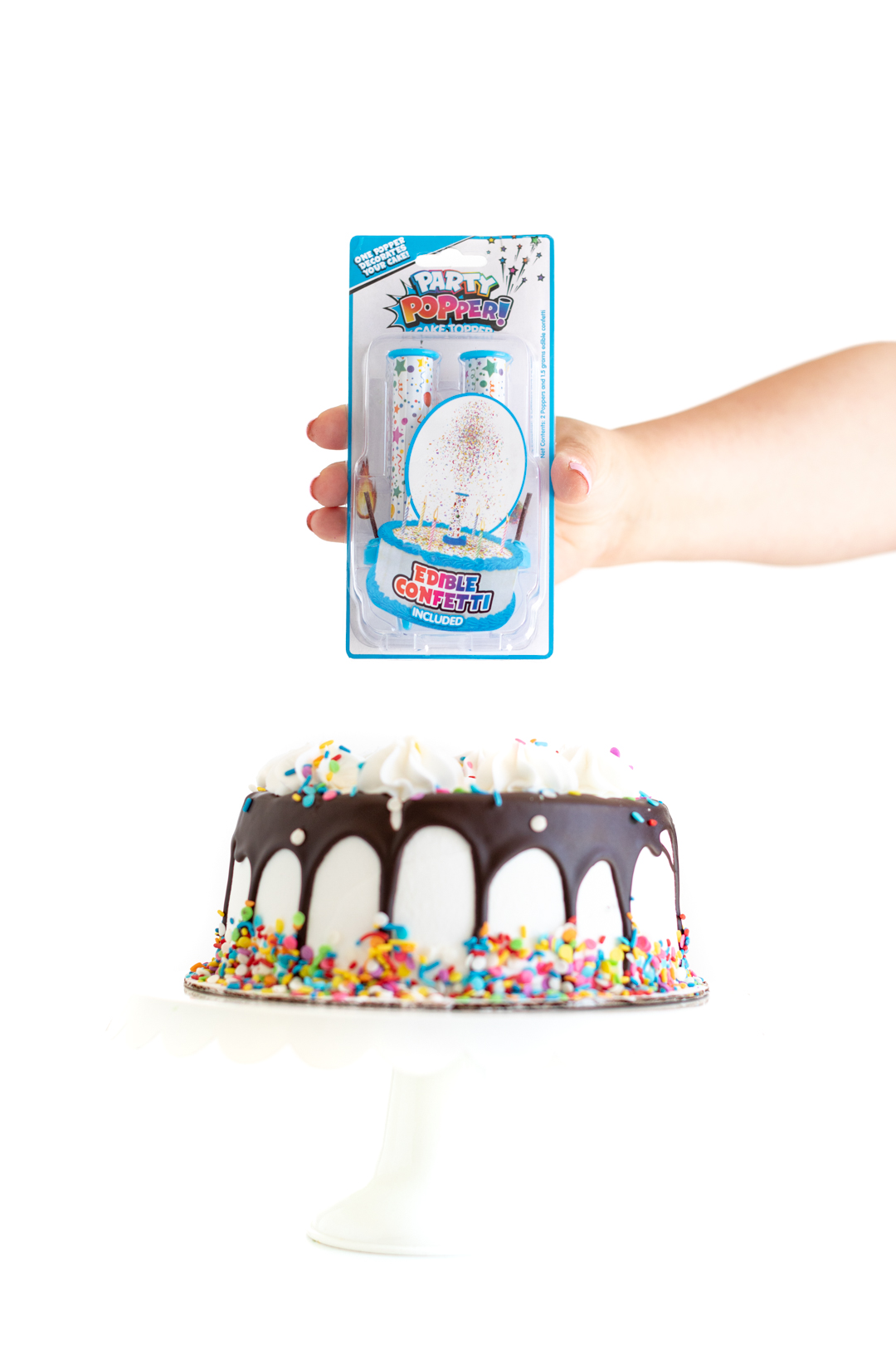 holding a package of party popper! cake topper candle placed on top of a white birthday cake with sprinkles and a chocolate drip.