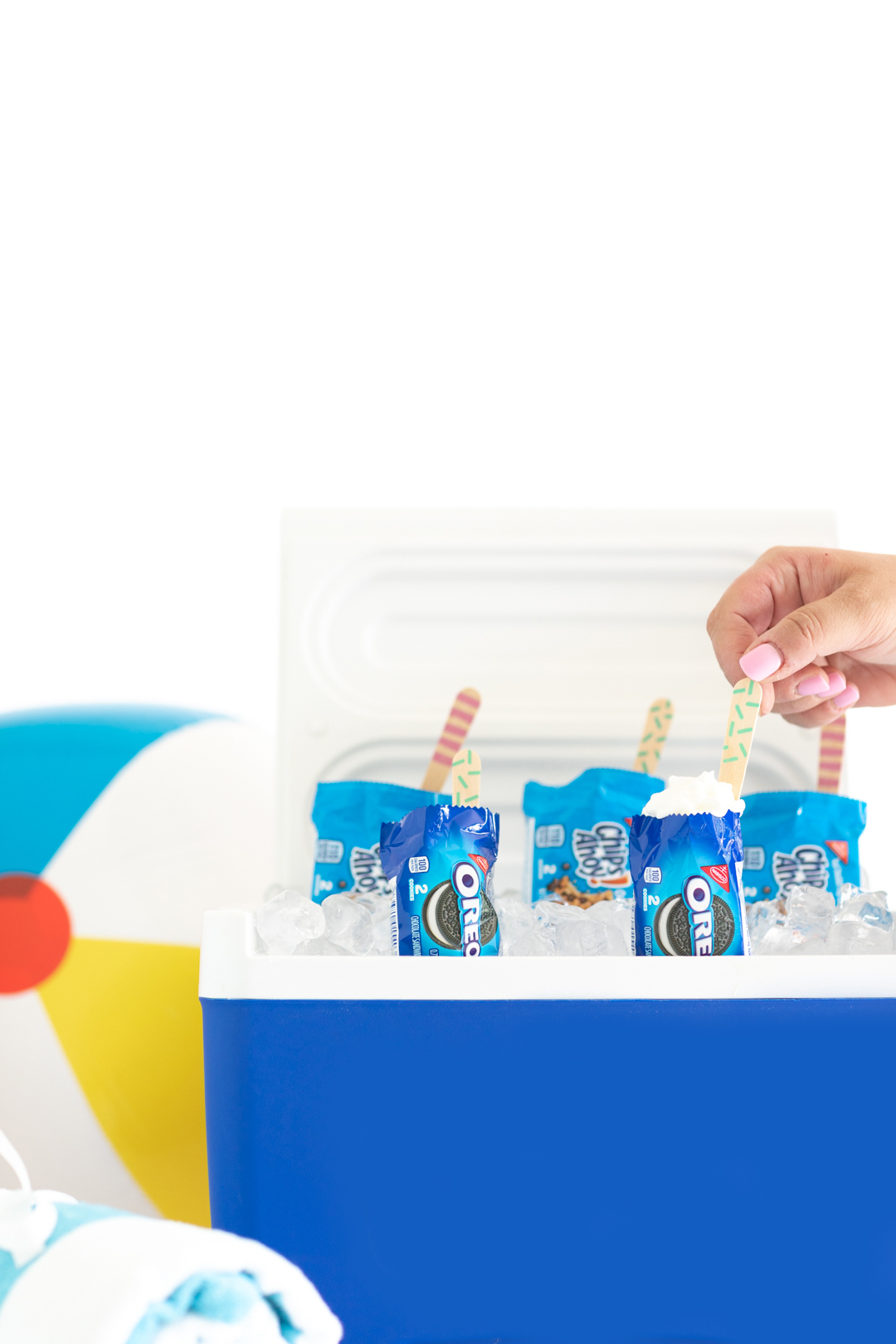 adding small wooden spoons to mini desserts being served out of a cooler
