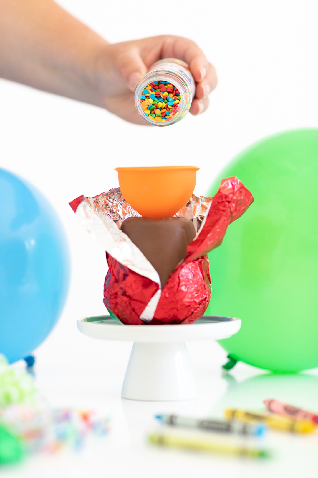 woman pouring sprinkles into a food funnel to get sprinkles into a hollow chocolate apple