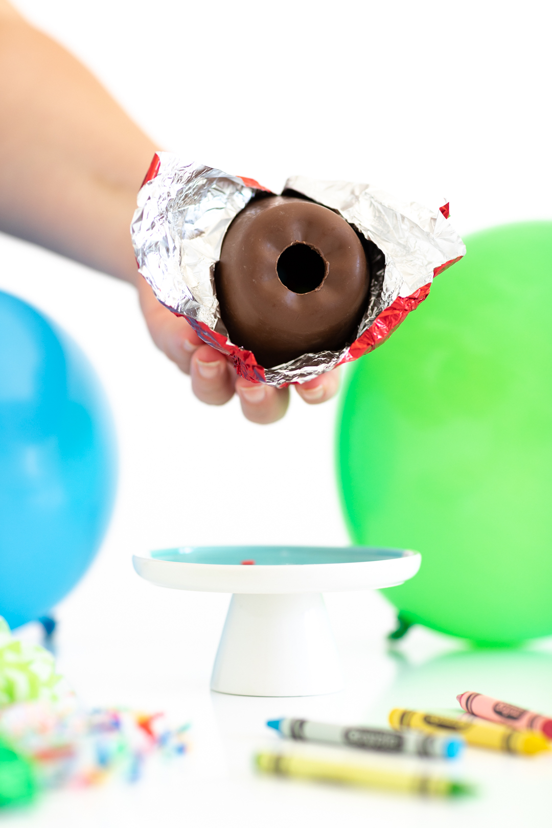 woman holding hollow chocolate apple with hole in the center