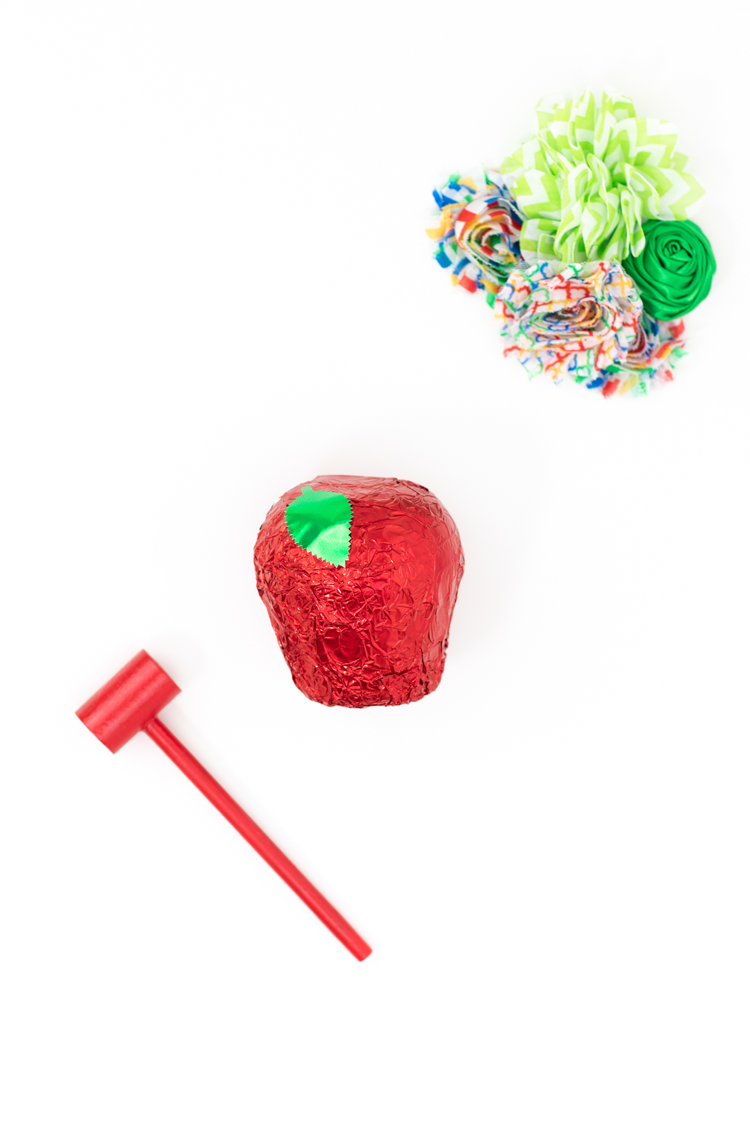 foil wrapped chocolate apple near a mini mallet to smash it with to reveal treats inside
