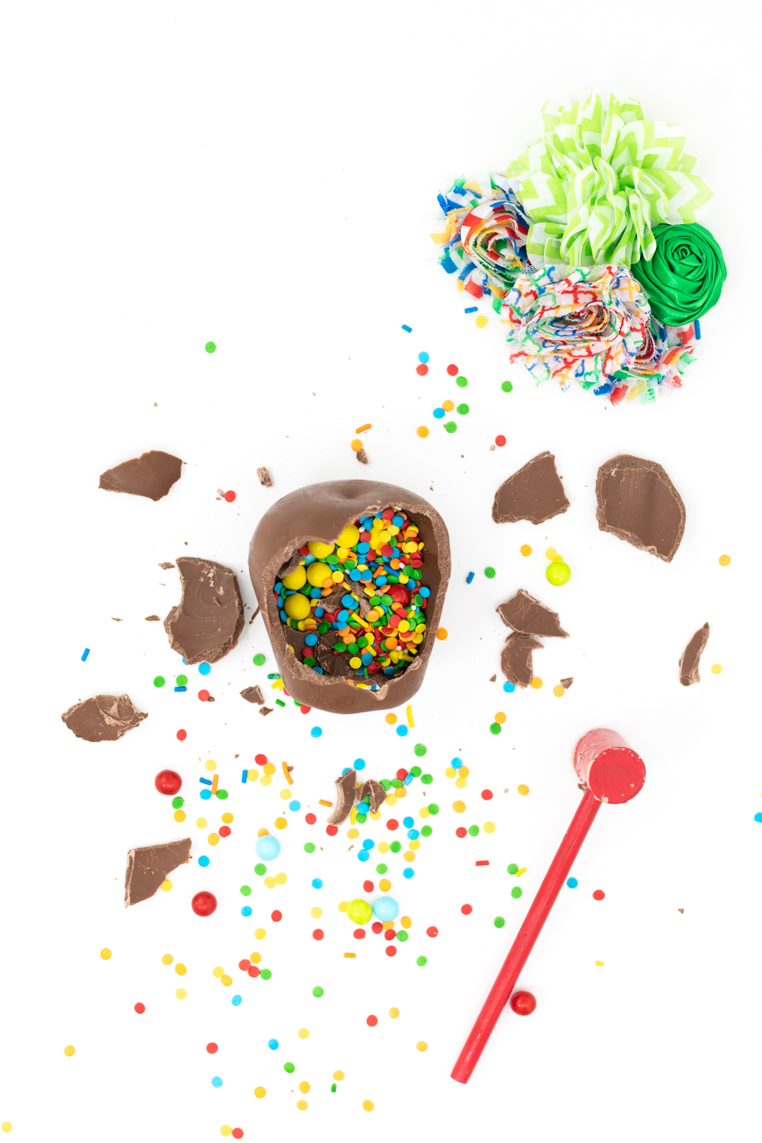 smashed chocolate pinata apple with confetti sprinkles and small candies all over