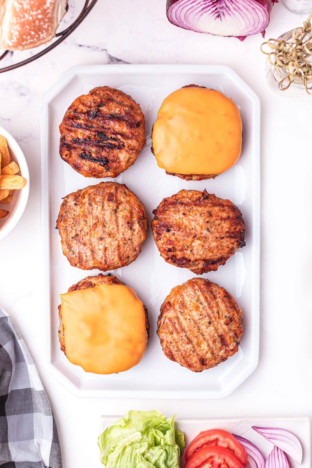 grilled chicken burgers on a platter. Some with melted cheese with condiments and burger toppings all around