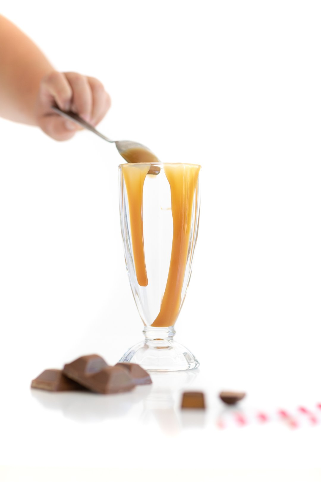 adding caramel to a glass to decorate
