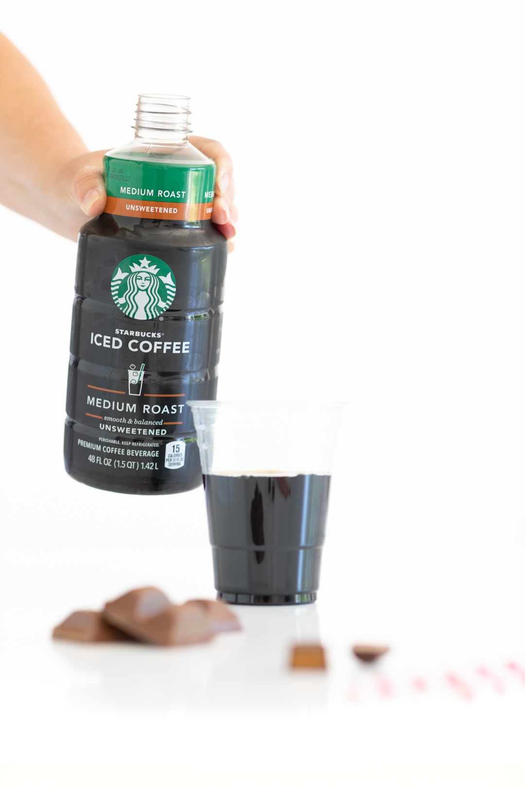 pouring a glass of starbucks iced coffee into a cup