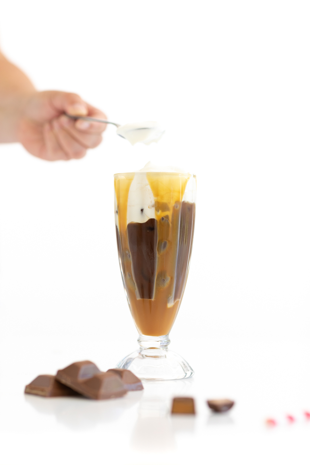 adding frothy cream to iced coffee in a glass