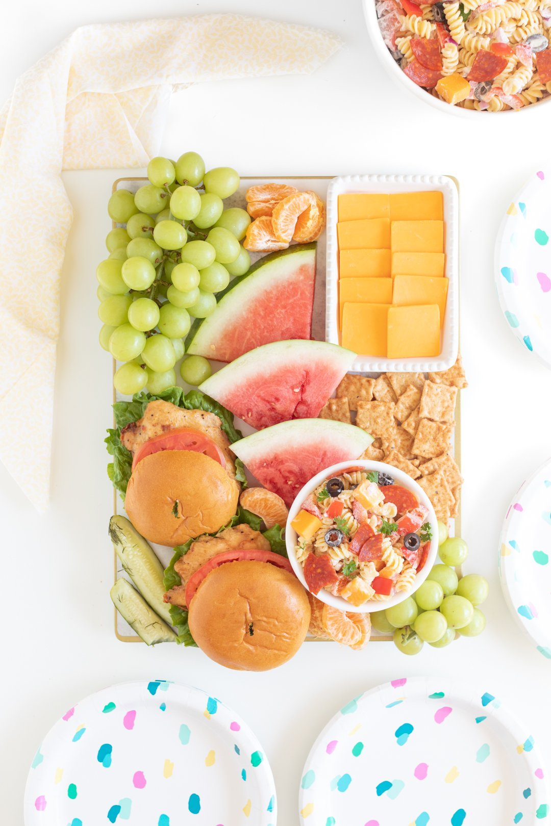 bbqterie board with grilled chicken sandwiches on buns, sliced watermelon, fruits, pasta salad, cheese and crackers