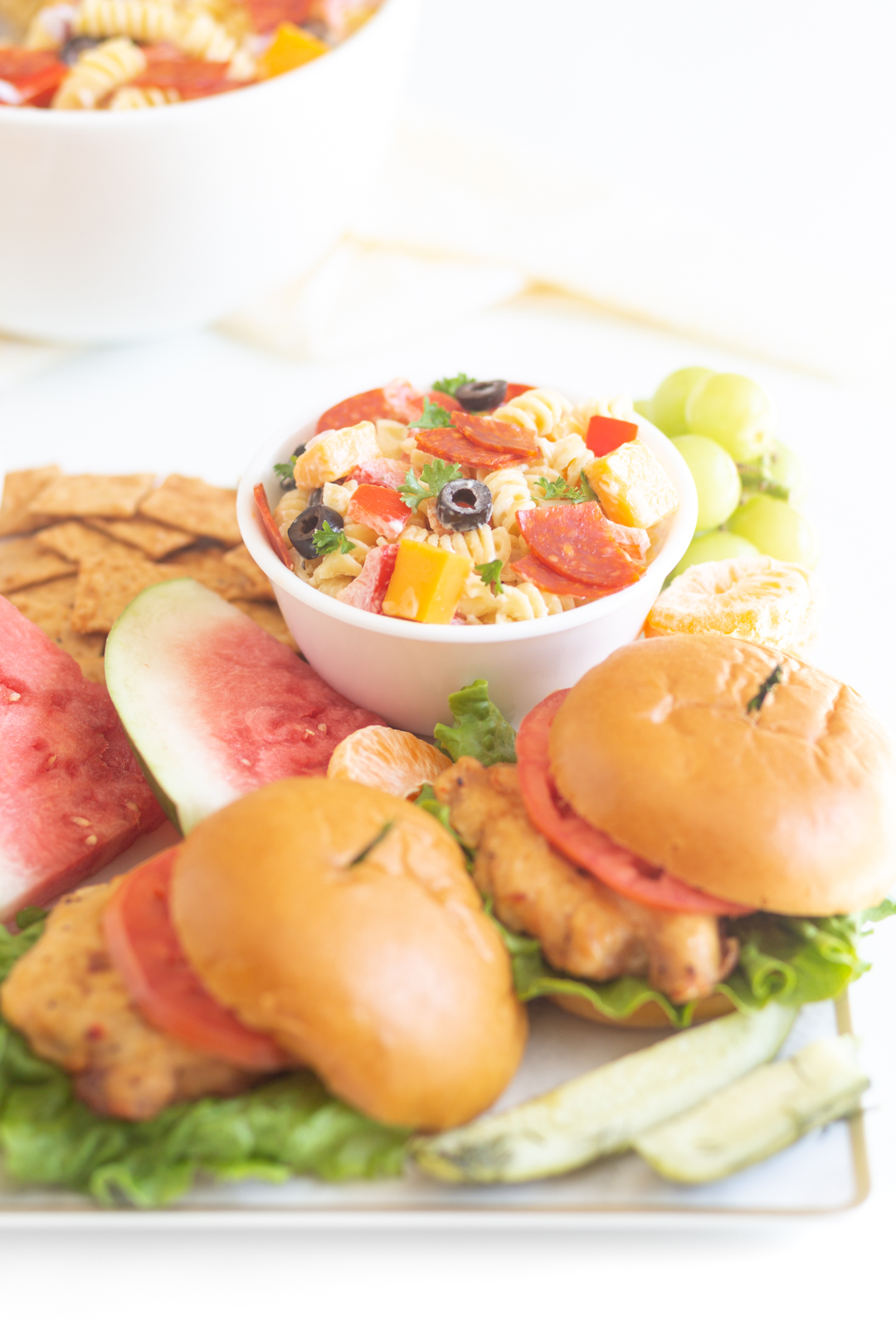 tray of barbecue items with chicken sandwiches, bowl of pasta salad, watermelon and more