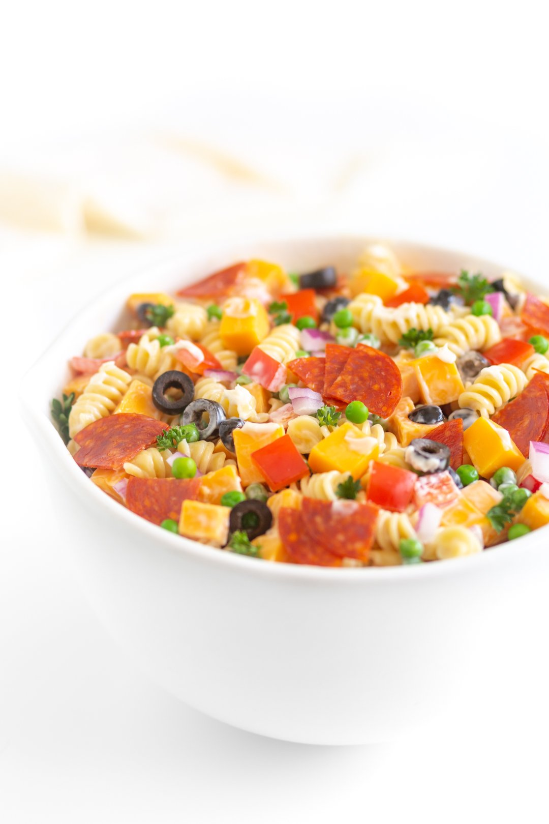 bowl of pasta salad with spiral pasta, pepperoni, black olives, onions