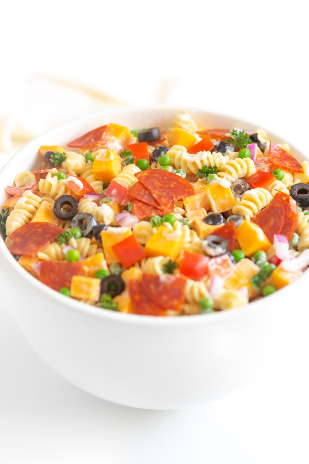 bowl of creamy pasta salad loaded with ingredients from chopped pepper to sliced pepperoni