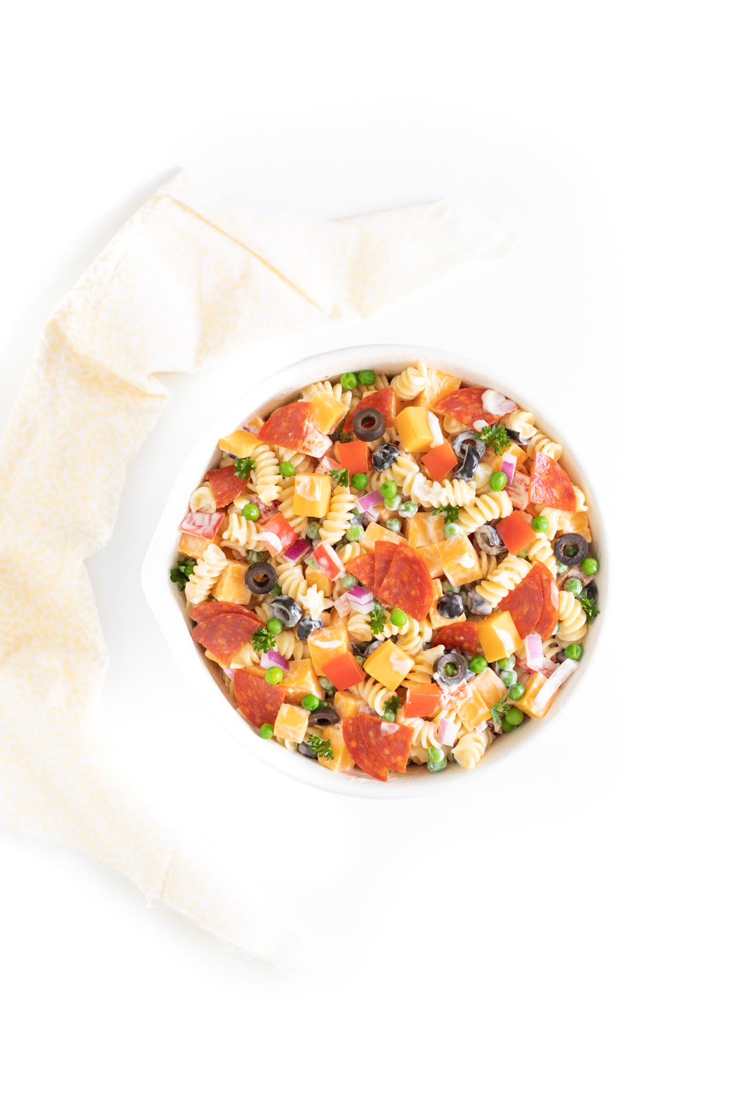 overtop view of a classic style creamy pasta salad with cheese and pepperoni
