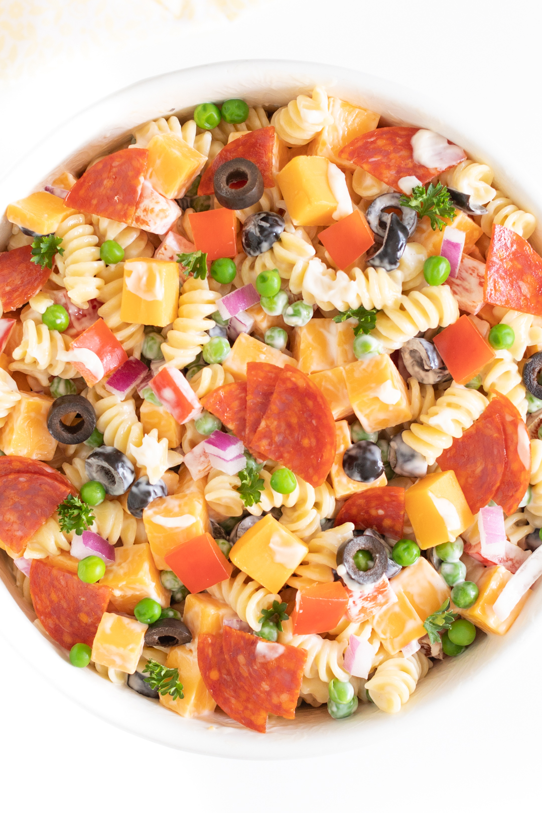 up close of pasta salad in a bowl topped with cheese chunks, pepperoni quarters, parsley, chopped red peppers and more.