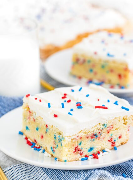 close up view of a single sugar cookie bar with cream cheese frosting and sprinkles on top served on a small dish. Milk in background
