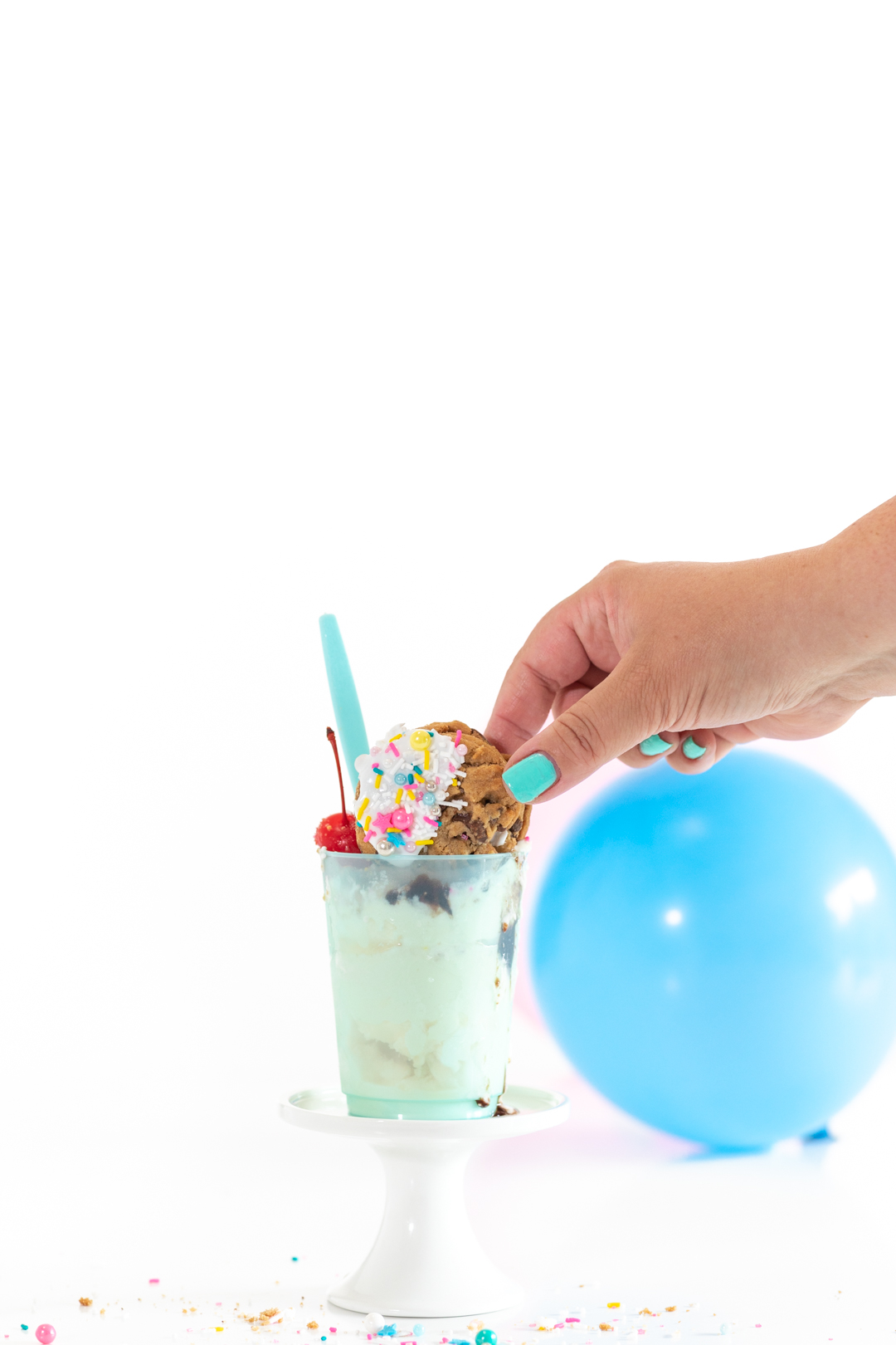 woman grabbing cookie off of the top of an ice cream sundae