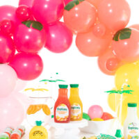 tropical refreshment table decorated with fun balloon garland with tropical inspired juice flavors