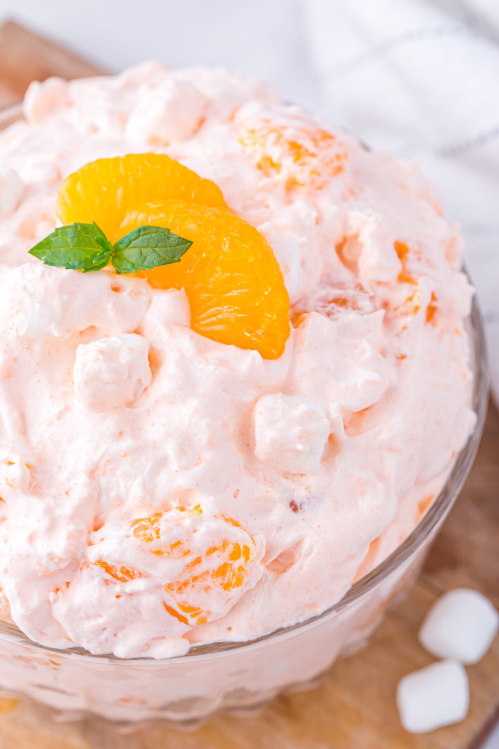 fluffy orange dessert made with whipped topping and canned mandarin orange. Topped with slice of mandarin orange and fresh mint sprig.