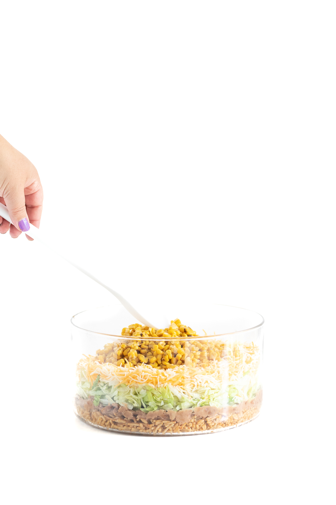 adding a layer of canned corn onto a mexican salad