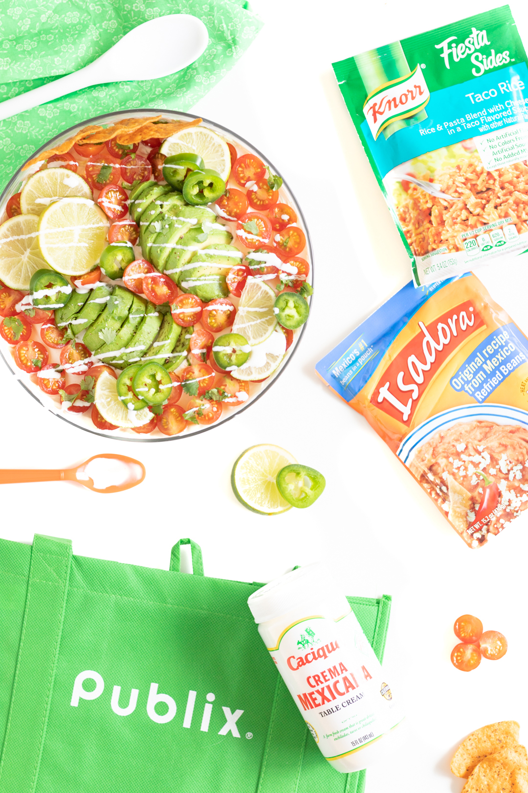 Publix reusable shopping bag, layered Mexican salad in a bowl, Knorr Sides Rice Packet and spoon.