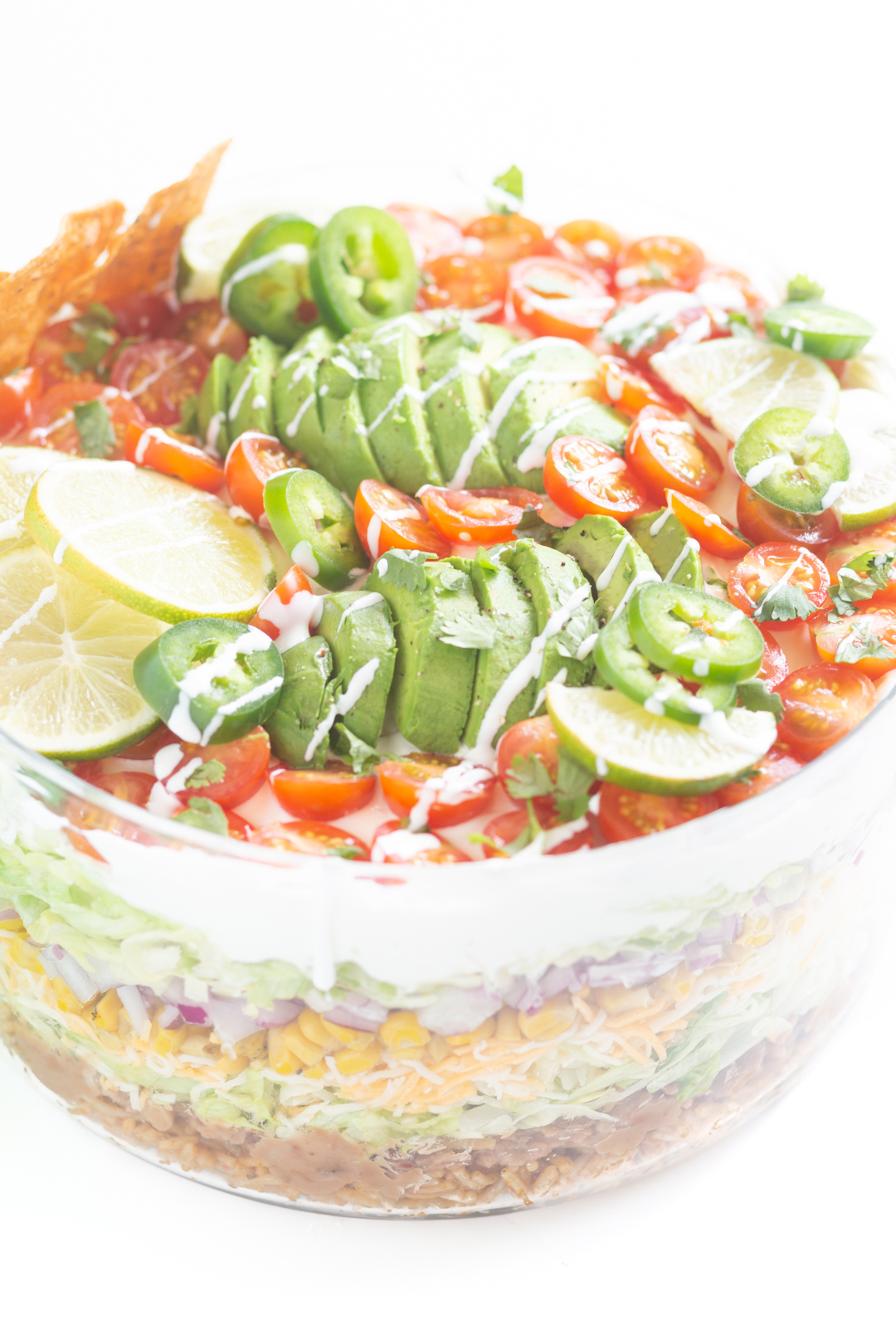 view of top of layered salad with sliced avocados, sliced cherry tomatoes and lime slices.