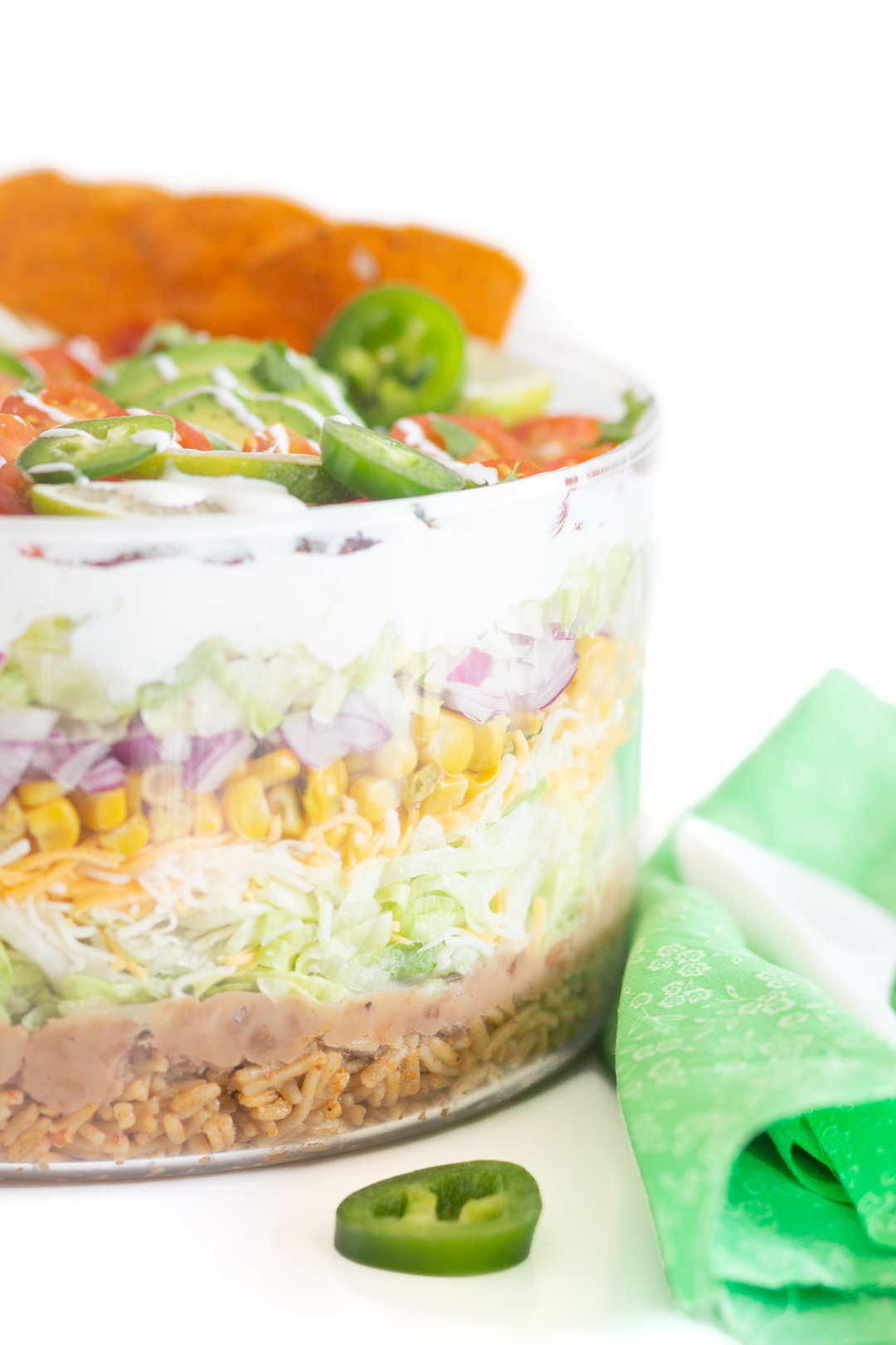 up close view of layers of salad in a glass serving bowl.