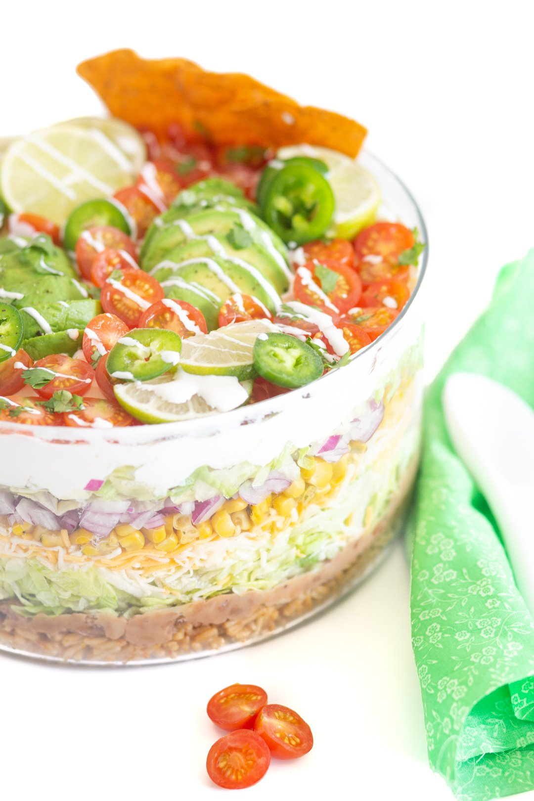 gorgeous mexican salad with pretty green cloth napkin and white spoon next to it