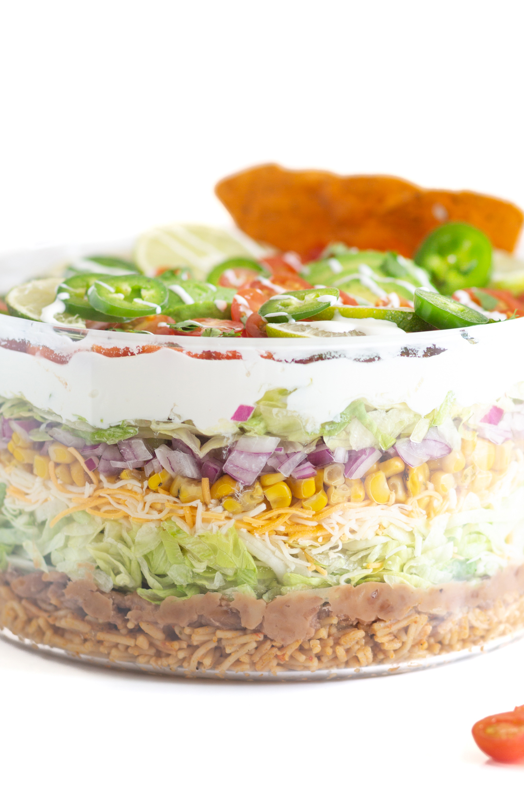 layered Mexican salad with refried beans, shredded lettuce, shredded cheese, diced onions, sour cream, canned corn.