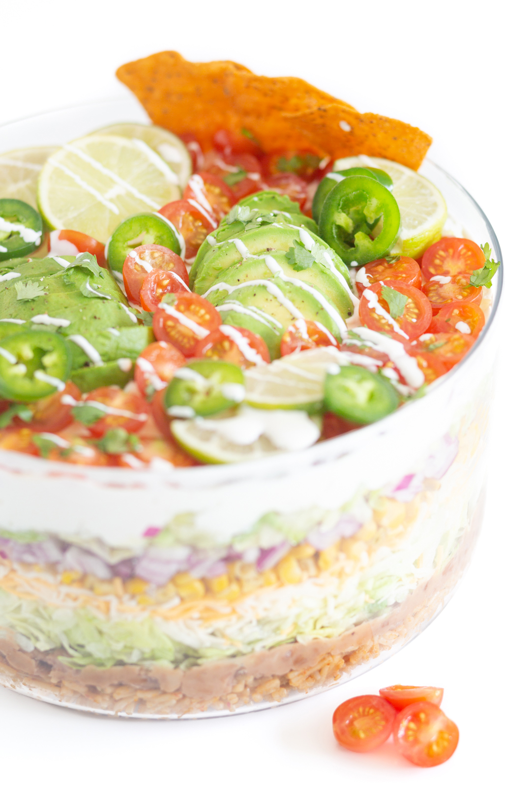 up close view of a pretty mexican layered salad topped with sliced avocado and halved cherry tomatoes, lime slices, cilantro