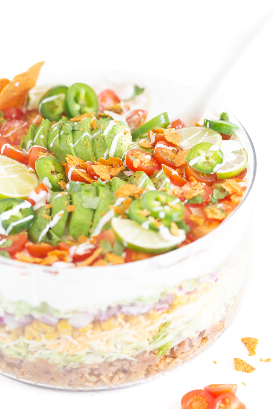 layered Mexican salad topped with fresh avocado, crushed nacho tortillas, cherry tomatoes, jalapeños, lime slices