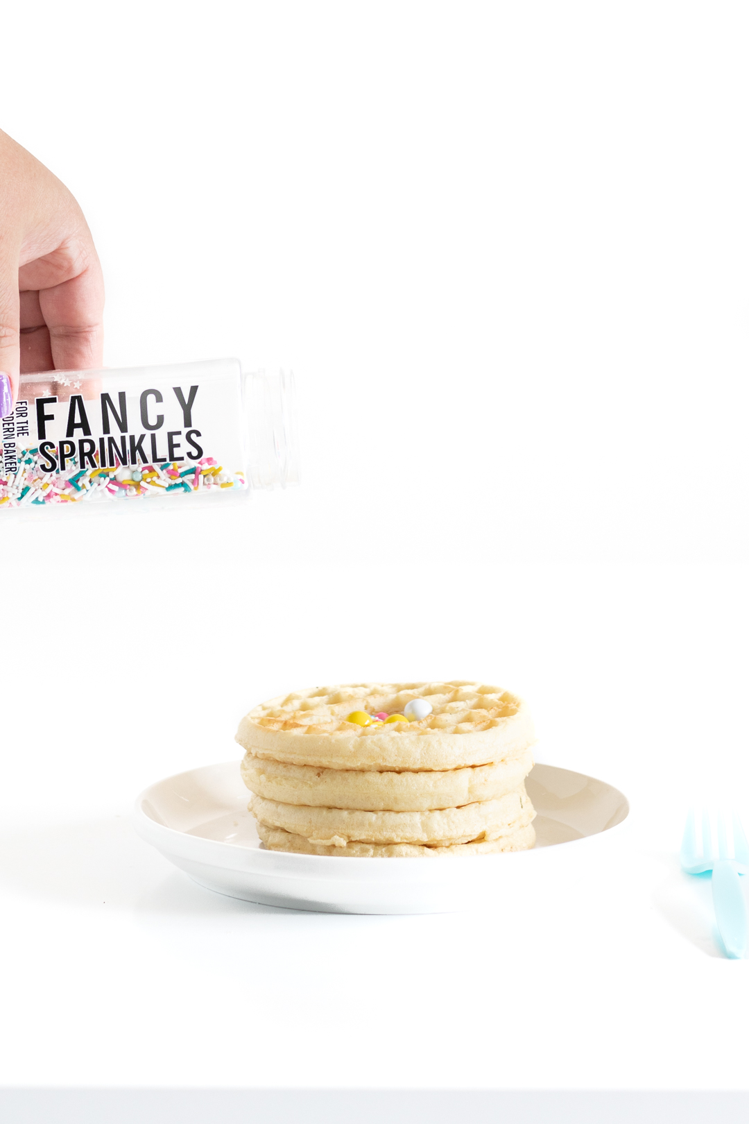 pouring sprinkles into a stack of waffles with the center hollowed out