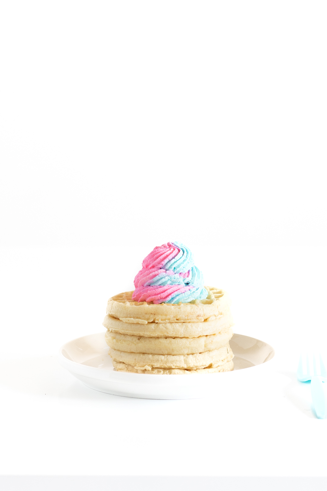 stack of waffles on a white plate with a lip topped with pink and blue swirled whipped cream