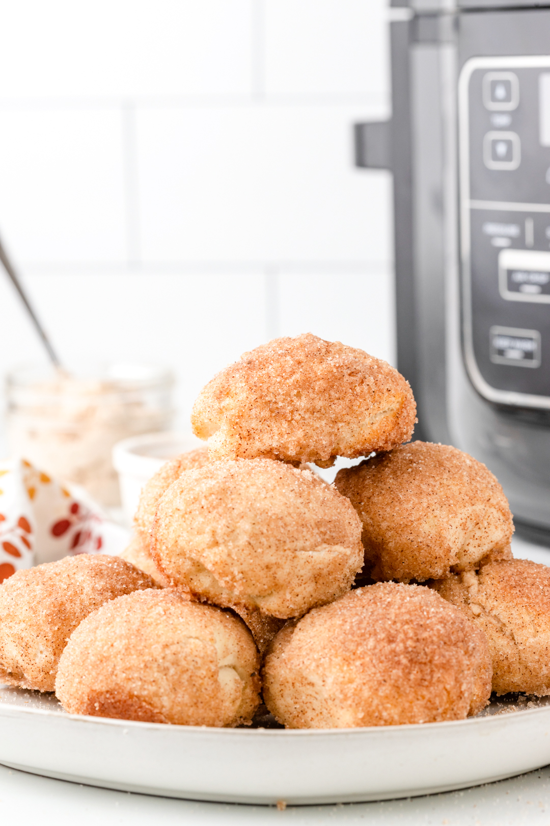 stack of donut bites with air fryer in the background