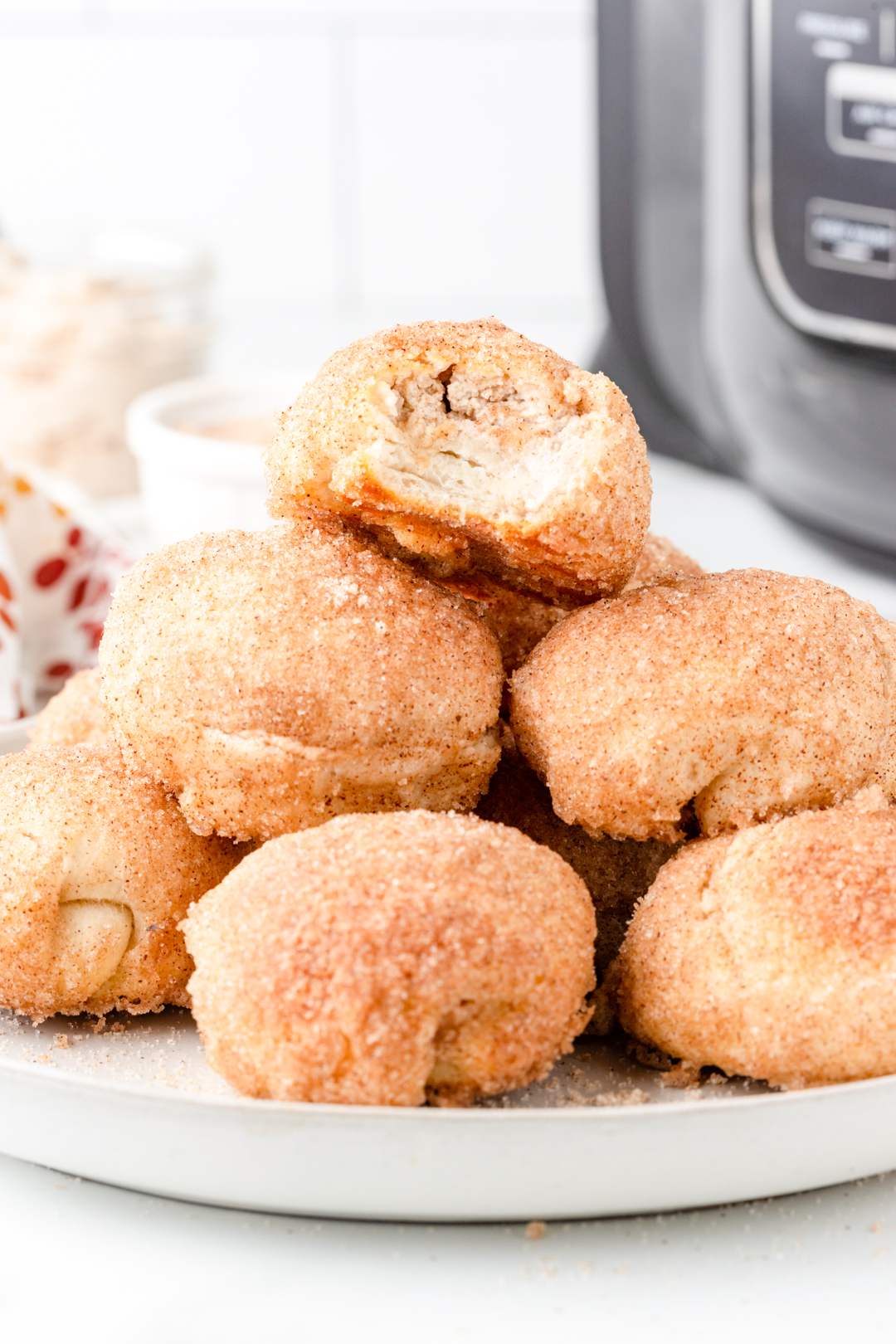 plate of donut bites with one on top with a bite taken out of it