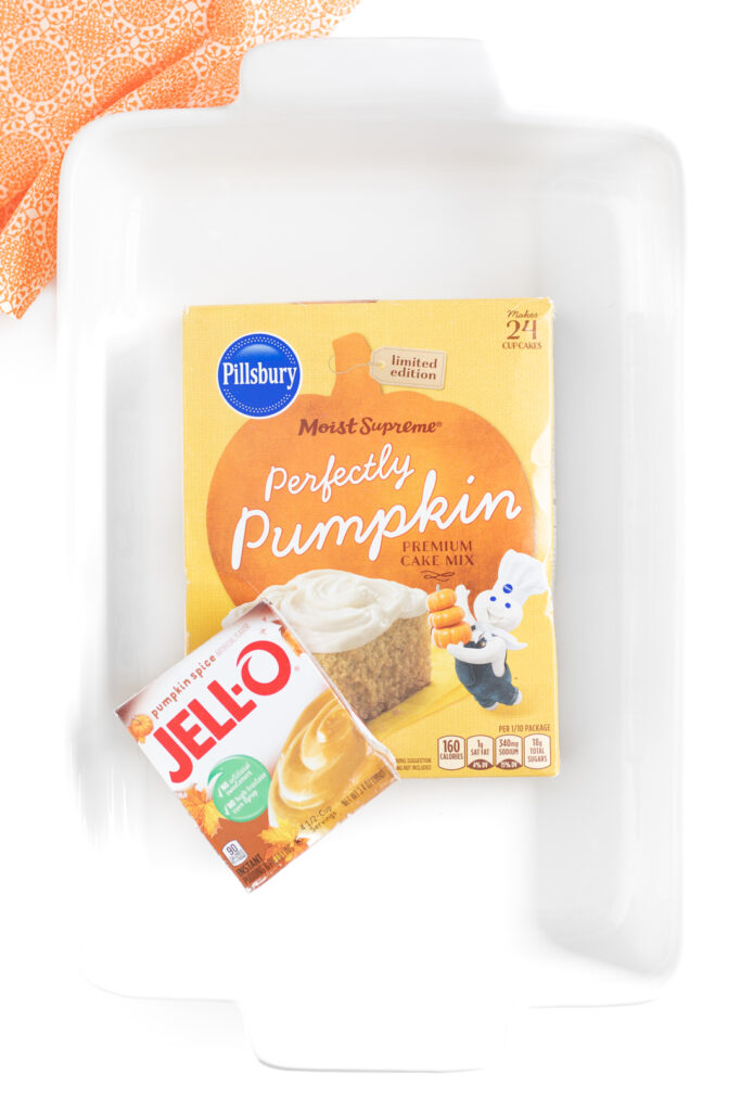 over the top photo of white baking dish with pillsbury perfectly pumpkin cake box and jello pumpkin spice instantly pudding mix box inside.