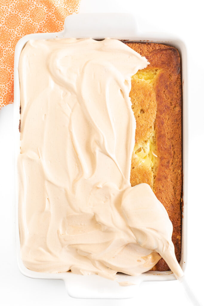 overhead photo of pumpkin cake being frosted with pumpkin spice pudding mixed with cool whip